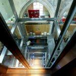Van den Beemd maakt exclusieve glazen panorama liftschacht met RVS rotules in een oud Klooster. Luxeuze liftschacht in 5-sterren Kruisherenhotel Maastricht.